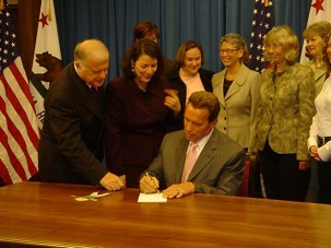 Group of supporters around Governor signing the bill