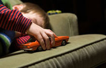 Child playing with toy car on a sofa