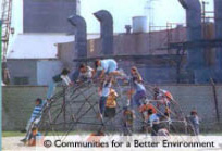 Children playing on playground in front of a factory