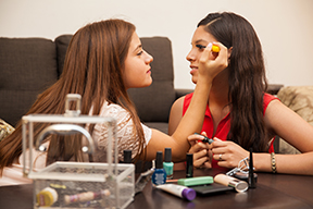 Two teen girls, one applying make-up to the face of the other girl