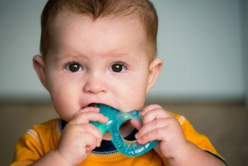 Baby with a plastic toy in his or her mouth