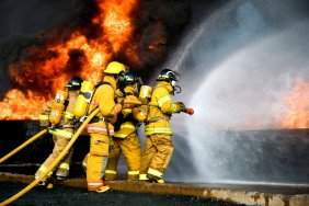 Firefighters fighting flames, wearing full protective suits and holding large hoses spraying water