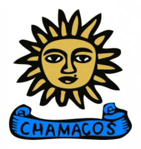 """Chamacos logo shows a drawing of a sun with a face on it, and beneath this, a scroll with the word """"chamacos"""""""