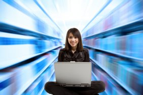 Young woman seated facing a laptop, with shelves of books zooming by on both sides